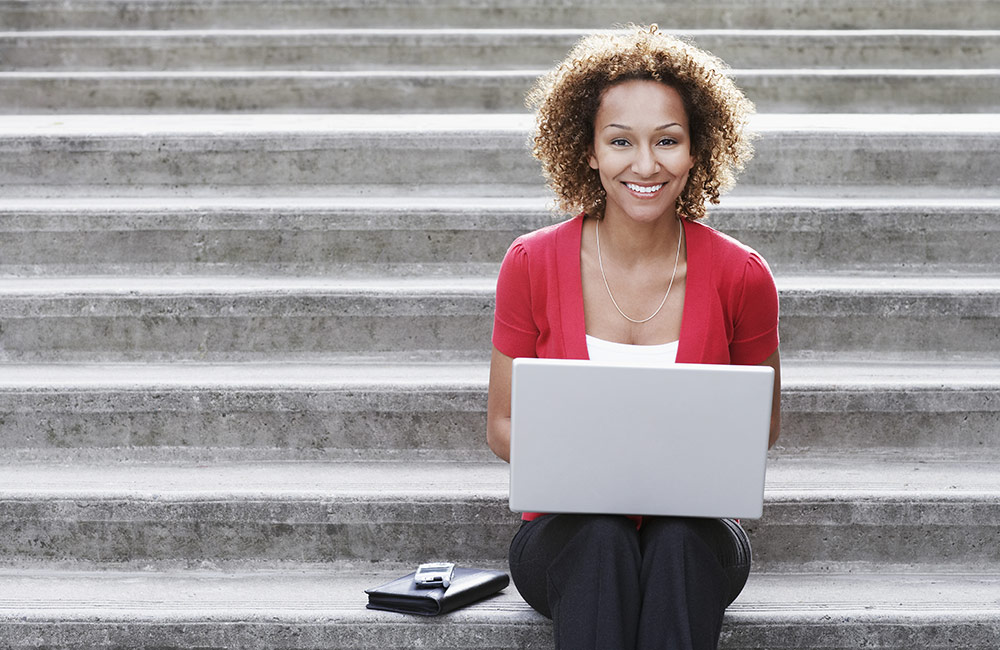 A happy woman sits with a laptop working on her resume