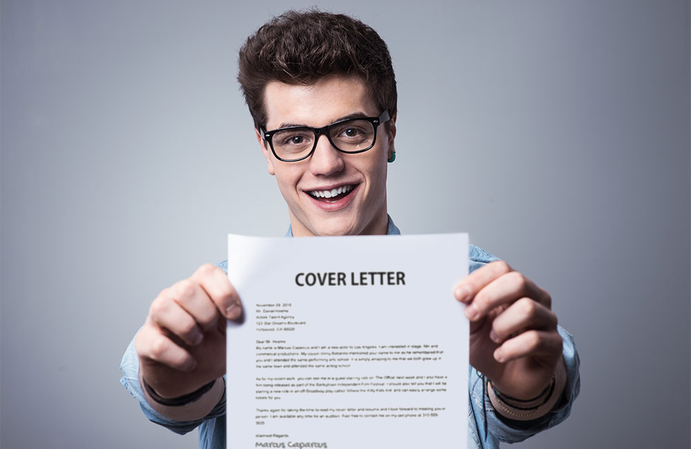 A goofy guy holds his cover letter in front of him