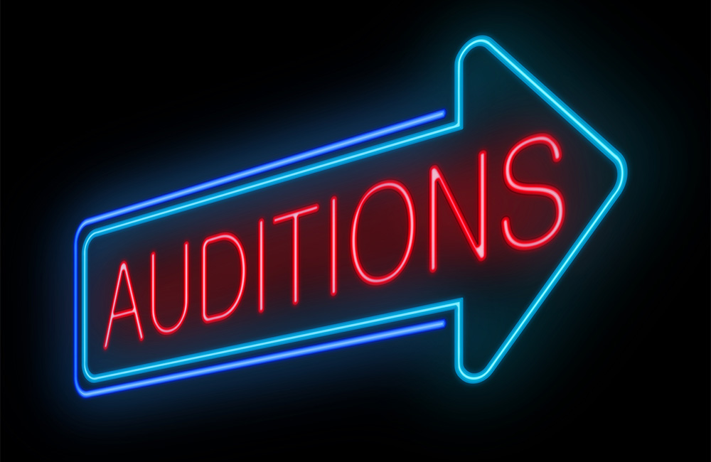 A neon arrow sign points toward auditions