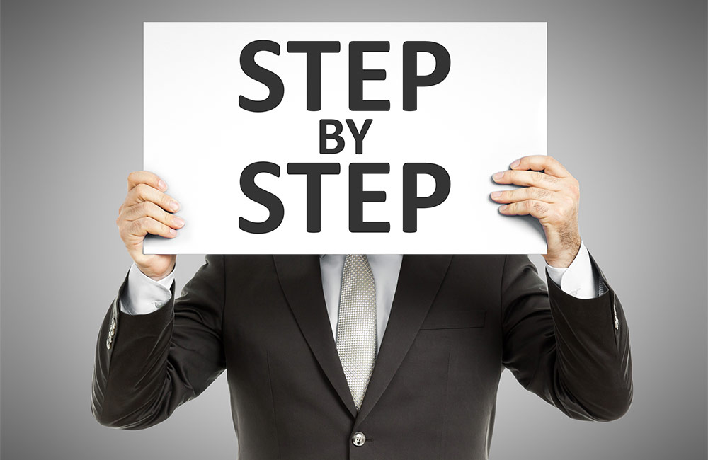 Man holding step by step sign