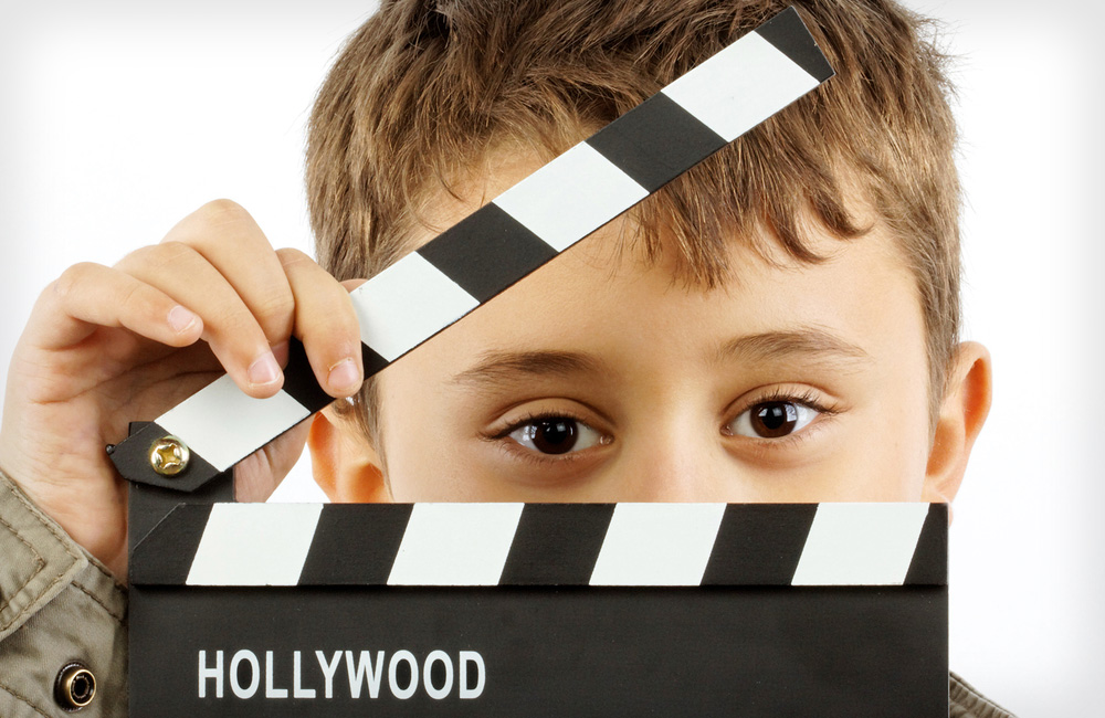 A young child stands behind a movie slate