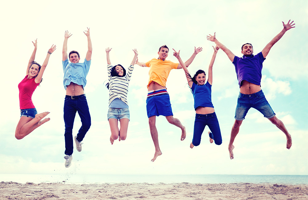 Young adults jumping and celebrating on a beach