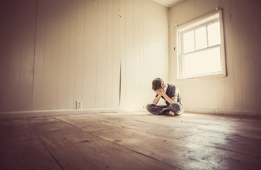 A child sits alone looking depressed