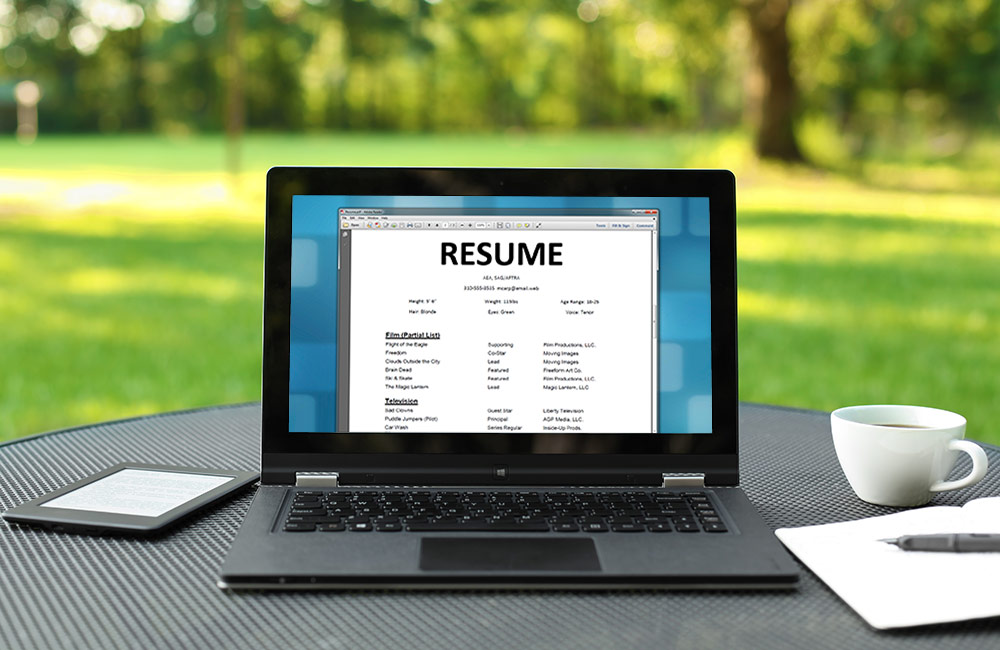A laptop screen shows a resume word document