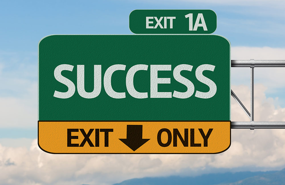 Highway exit sign pointing toward Success