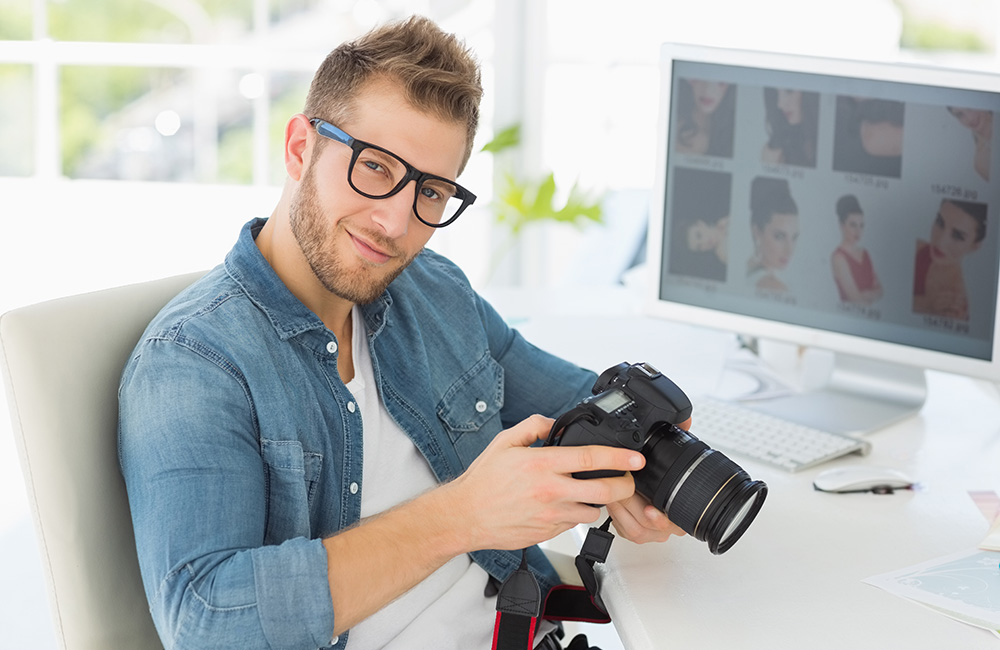 A male photographer holding a camera