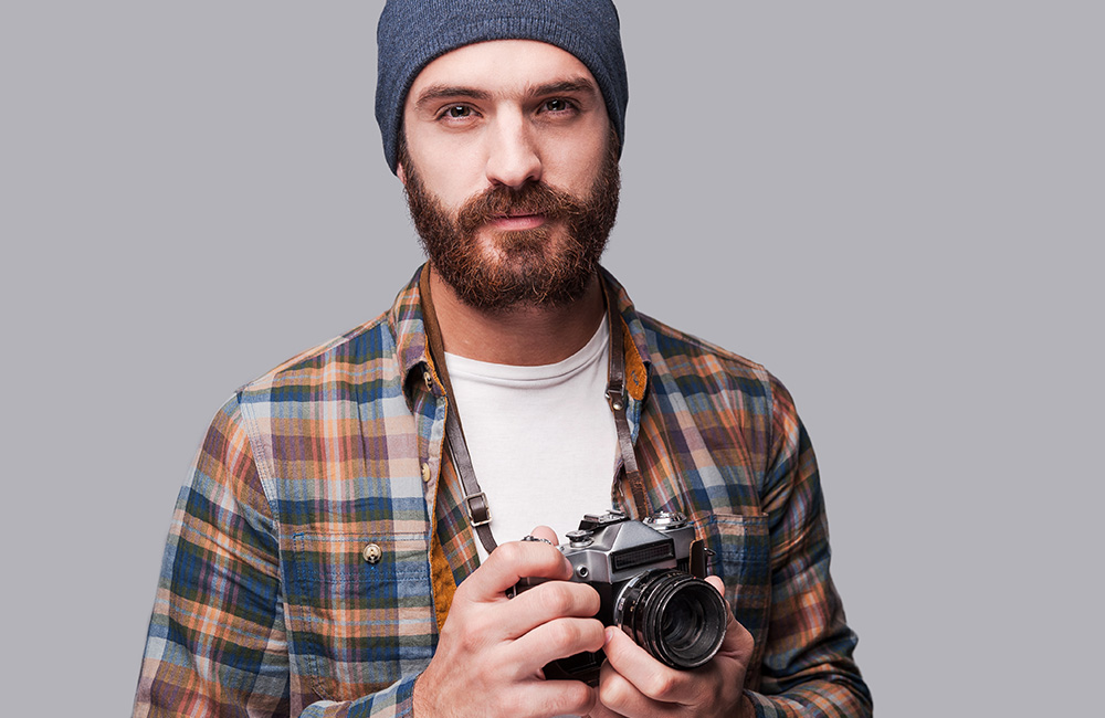 A hipster photographer holds a camera