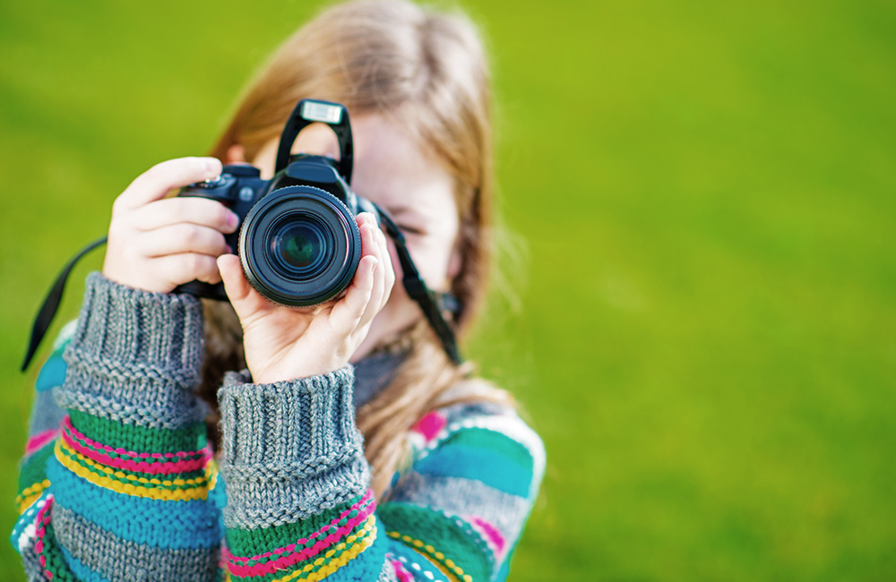 A young girl takes photos with her camera